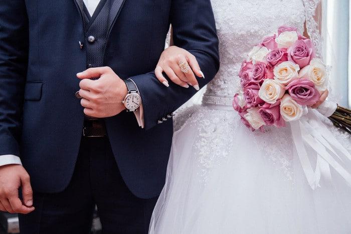 Wesele - państwo młodzi z zegarkiem, bukietem i pierścieniem